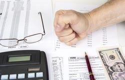 Beräkning av nummer för inkomstskattretur med pennan, exponeringsglas och räknemaskinen arkivbilder
