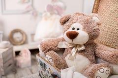 Berçário com um urso de peluche do brinquedo em uma mala de viagem Fotos de Stock