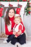 Beröm för jul eller för nytt år Den lyckliga modern omfamnar dottern som placerar nära en spis för vit jul med att lagerföra för  Arkivbild
