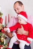 Beröm för jul eller för nytt år Den unga härliga fadern rymmer den lilla dottern på iklädd röd festlig dräkt för händer av gn Royaltyfri Foto