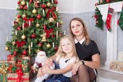 Beröm för jul eller för nytt år Lycklig moder och dotter som omfamnar på julgranen med xmas-gåvor En spis med christm Arkivfoto