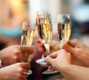 Beröm. Folk hållande exponeringsglas av champagne Royaltyfri Foto