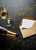 Beröm med champagne och kortet på den svarta tabellen arkivfoton