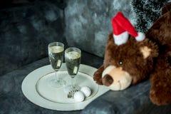Beröm - nallebjörn med en santa hatt och två exponeringsglas av champagne på en vit platta på en fåtölj med böcker royaltyfri foto