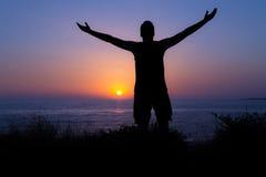 Beröm och dyrkan vid havet på solnedgången Royaltyfria Bilder