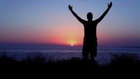 Beröm och dyrkan vid havet på solnedgången lager videofilmer