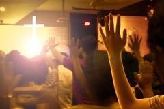 Beröm- och dyrkanbegrepp: Händer som lyfts i spänning och beröm på samtidakyrkakonserten och ljusa ljus arkivfoton