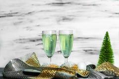 Beröm - två exponeringsglas av grön champagne på en tabell arkivfoton