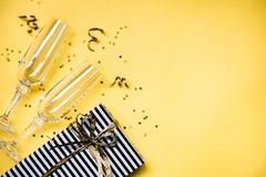 Berömbakgrund - bästa sikt av två chrystal champagneexponeringsglas, en gåvaask som slås in i svartvitt randigt papper, band royaltyfri fotografi