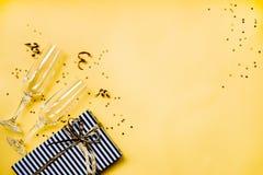 Berömbakgrund - bästa sikt av två chrystal champagneexponeringsglas, en gåvaask som slås in i svartvitt randigt papper, band royaltyfria foton