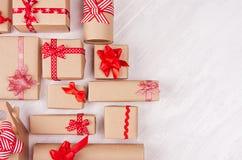 Berömbakgrund för nytt år - pappers- gåvor för hemlagat hantverk med röda band och pilbågar på den vita träplankan, bästa sikt, g royaltyfria bilder