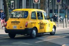 Berömd brittisk gul taxitaxi på den London gatan på solig dag royaltyfri bild