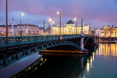 Berömd bro och universitet längs Rhone River på natten, Lyon Arkivbild