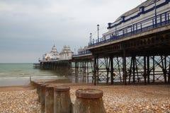 Berömd Eastbourne pir och strand i molnig dag Östliga Sussex som är engelsk Fotografering för Bildbyråer
