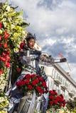 Berömd karneval av Nice, blomma`-strid En kvinnaunderhållare med röda blommor royaltyfri fotografi