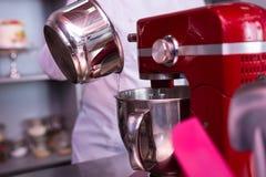 Berömd kock för professionell som använder den moderna röda matlagningmaskinen arkivfoton