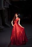 Berömd kvinna för skönhet i den utomhus- röda klänningen Arkivbild