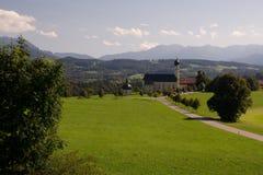 Berömd kyrka med fjällängarna i bakgrunden Fotografering för Bildbyråer