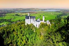 Berömd Neuschwanstein slott, slott för nypremiär för århundrade för th 19 romansk på en ojämn kulle ovanför byn av Hohenschwangau royaltyfria bilder
