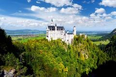Berömd Neuschwanstein slott, slott för nypremiär för århundrade för th 19 romansk på en ojämn kulle ovanför byn av Hohenschwangau royaltyfria foton