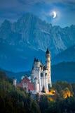 Berömd Neuschwanstein slott på natten med månen och belysning royaltyfri fotografi