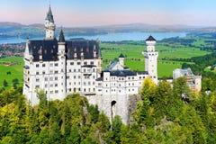 Berömd Neuschwanstein slott, sagaslott på en ojämn kulle ovanför byn av Hohenschwangau nära Fussen royaltyfri fotografi