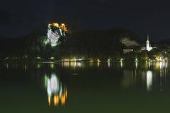 Berömd slott och St Martins Parish Church i natten på Bled sjön Fotografering för Bildbyråer