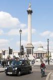 Berömd svart cab som kör vid Trafalgar Fyrkant Royaltyfri Bild