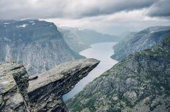Berömd trekking destination Trolltunga i Odda, Norge, under den regniga dagen med molnen i himlen Fotografering för Bildbyråer