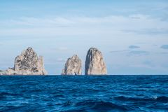 Berömda havsbuntar med bågen, faraglioni, av kusten av Capri i fjärden av Naples på medelhavet, Italien royaltyfri foto