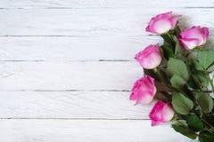 Berömram med rosa rosor på vita plankor Arkivfoto