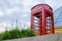 Berömt engelskt rött telefonbås med molnig dag Arkivbild