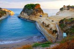 Berömt kärleksaffärstrand för kanal D 'med den härliga steniga kustlinjen, i att förbluffa det blåa Ionian havet på soluppgång i  arkivfoton