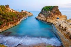 Berömt kärleksaffärstrand för kanal D 'med den härliga steniga kustlinjen, i att förbluffa det blåa Ionian havet på soluppgång i  royaltyfri bild