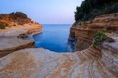 Berömt kärleksaffärstrand för kanal D 'med den härliga steniga kustlinjen, i att förbluffa det blåa Ionian havet på soluppgång i  royaltyfria bilder