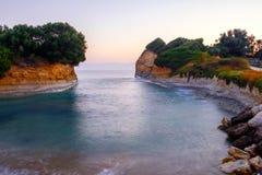 Berömt kärleksaffärstrand för kanal D 'med den härliga steniga kustlinjen, i att förbluffa det blåa Ionian havet på soluppgång i  arkivbilder
