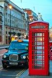 Berömt rött telefonbås och taxitaxi i London Arkivbild