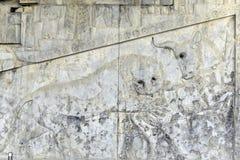 Berömt snida för baslättnad av ett lejon som jagar en tjur i den Persepolis världsarvet Royaltyfri Foto
