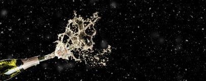 Berömtema med att plaska champagne på svart bakgrund med snö och fritt utrymme Jul eller nytt år, valentindag royaltyfri bild