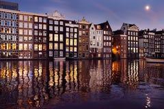 Berühmte tanzende Häuser des Damrak-Kanals in Amsterdam nachts stockfotografie