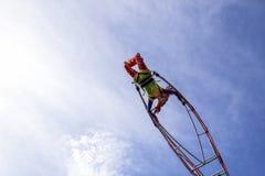 Berühmter Karneval von Nizza, Blumen ` Kampf Eine Akrobatfrau mit Clownkostüm auf Himmelhintergrund Stockfoto