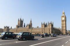 Berühmtes schwarzes Fahrerhaus, das durch Houses des Parlaments antreibt Lizenzfreie Stockfotografie