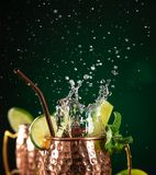 Berühmtes spritzendes alkoholisches Cocktail Moskau-Maultiers in den kupfernen Bechern stockbild