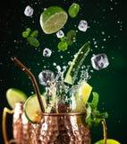 Berühmtes spritzendes alkoholisches Cocktail Moskau-Maultiers in den kupfernen Bechern lizenzfreie stockfotografie