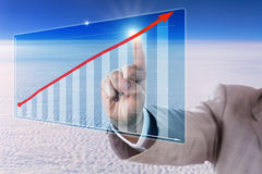Berühren eines Wachstums-Tendenz-Pfeiles in einem Balkendiagramm Lizenzfreies Stockfoto