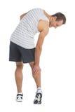 Berühren seines Beines Stockfotos