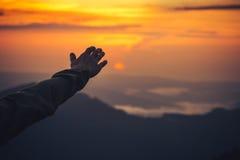 Berühren Sie die Himmelkonzept Mann-Hand und den Sonnenuntergang Stockfoto