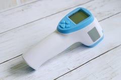 Berührungsfreier Infrarotthermometer auf dem weißen hölzernen Hintergrund, zum einer Körpertemperatur zu messen Gesundheitswesen  stockbilder