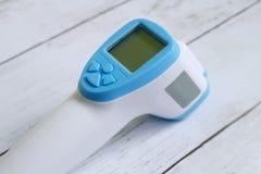 Berührungsfreier Infrarotthermometer auf dem weißen hölzernen Hintergrund, zum einer Körpertemperatur zu messen Gesundheitswesen  lizenzfreies stockfoto