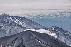 ?ber den einzigen Vulkanen der Wolken Vulkane von Kamchatka faszinieren Ihre Rätselhaftigkeit zieht viele Touristen von an stockbilder